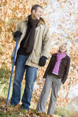 offset angle: Couple outdoors raking leaves and smiling (selective focus)