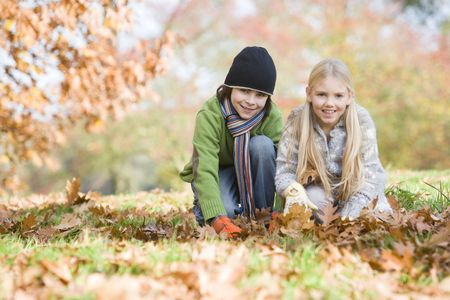 Two young children outdoors at park playing in leaves and smiling (selective focus)