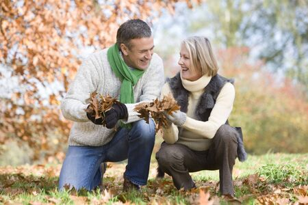 Couple outdoors holding leaves and smiling (selective focus) photo