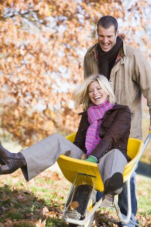 caucasoid race: Man outdoors pushing woman in wheelbarrow and smiling (selective focus)