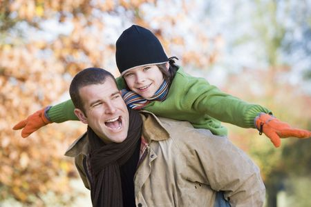 caucasoid race: Father piggybacking son outdoors at park and smiling (selective focus)