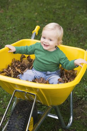 outdoors sitting in wheelbarrow smiling (selective focus) photo