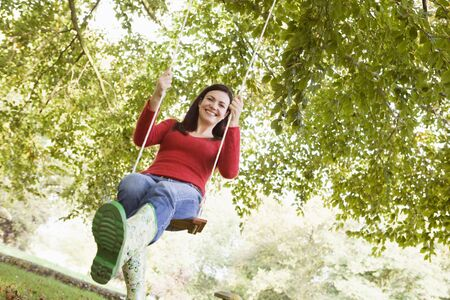 Woman outdoors on tree swing smiling (high keyselective focus) photo