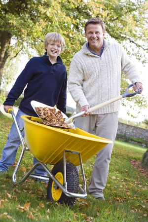 caucasoid race: Man outdoors with young boy shoveling leaves into wheelbarrow and smiling (selective focus) Stock Photo