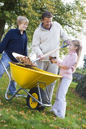 Father outdoors with two young children shoveling leaves into a wheelbarrow and smiling (selective focus) photo