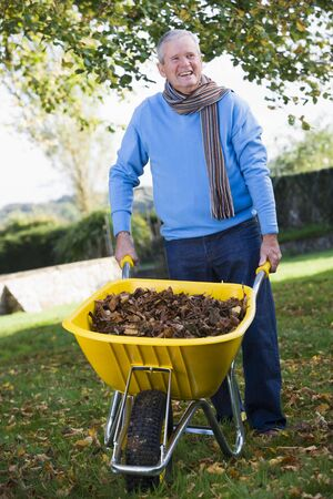 caucasoid race: Man outdoors with wheelbarrow full of leaves smiling (selective focus)