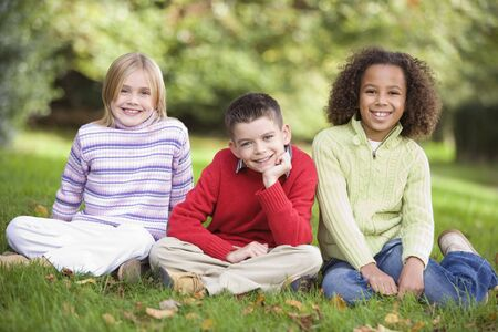tweeny: Three young children sitting outdoors in park smiling (selective focus)