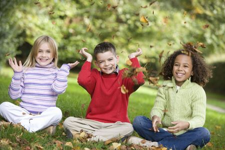 fallen leaves: Three young children sitting outdoors in park throwing leaves in air and smiling (selective focus) Stock Photo