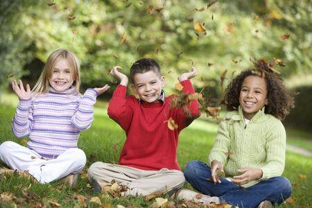 ni�os sentados: Tres ni�os peque�os sentados al aire libre en el parque tirando hojas en el aire y sonriente (atenci�n selectiva)
