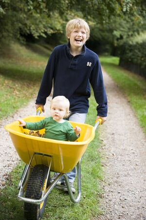 Young boy pushing  brother in wheelbarrow photo