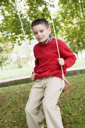 offset angle: Young boy outdoors on tree swing smiling (selective focus)