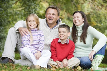Family sitting outdoors in park smiling (selective focus) Stock Photo - 3217694