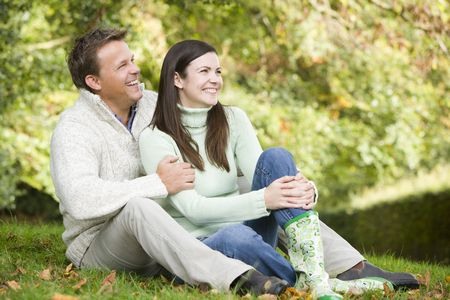 caucasoid race: Couple sitting outdoors smiling (selective focus)