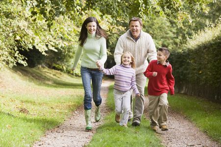 Family outdoors walking on path holding hands and smiling (selective focus) photo