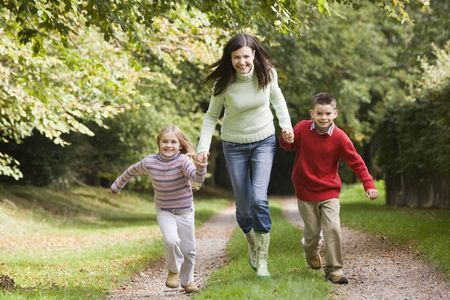 caucasoid race: Woman outdoors with two young children walking on path holding hands and smiling (selective focus)
