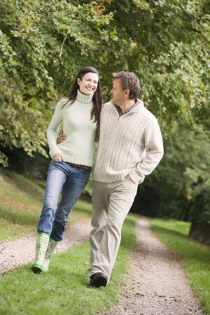 caucasoid race: Couple walking outdoors on path in park smiling (selective focus)