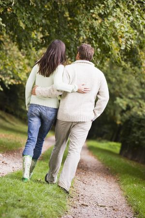 Couple walking outdoors on path in park (selective focus) photo