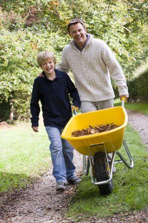 Father and son pushing wheelbarrow on path photo