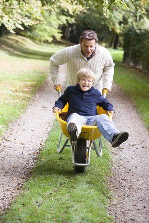 wheeling: Father pushing son in wheelbarrow Stock Photo