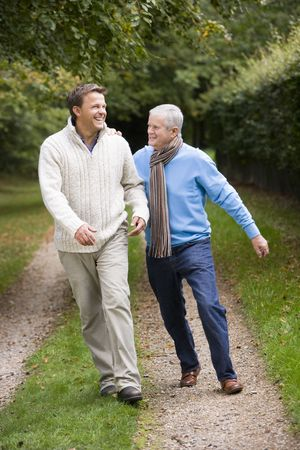 mid adult men: Senior father and son walking on path outdoors smiling