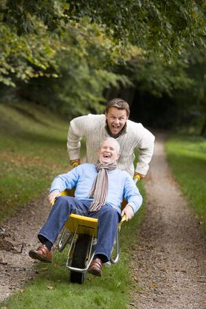 wheeling: Son pushing senior father in wheelbarrow Stock Photo
