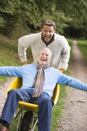 Son pushing senior father in wheelbarrow photo