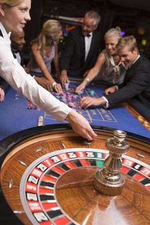 croupier: Group of people in casino playing roulette and smiling (selective focus)