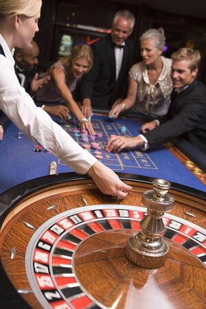 gambling parlour: Group of people in casino playing roulette and smiling (selective focus)