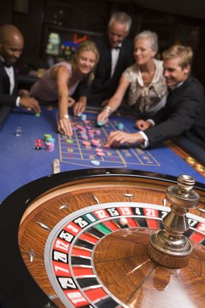 Group of people in casino playing roulette and smiling (selective focus) Stock Photo - 3194508