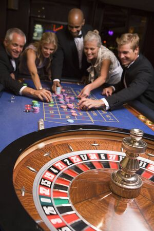 Group of people in casino playing roulette and smiling (selective focus) Stock Photo - 3194500