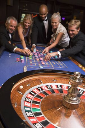 Group of people in casino playing roulette and smiling (selective focus) Stock Photo - 3194514