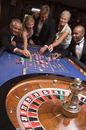 roulette wheels: Group of people in casino playing roulette and smiling (selective focus)