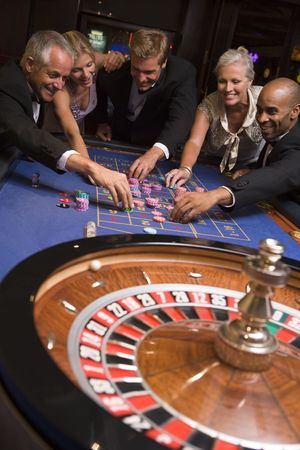 gambling parlors: Group of people in casino playing roulette and smiling (selective focus)