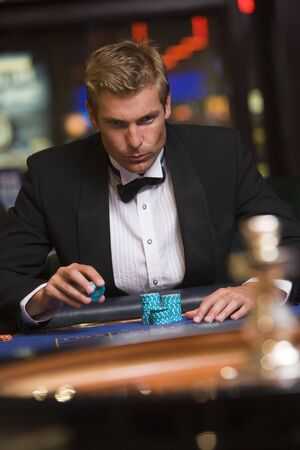 parlours: Man in casino playing roulette (selective focus) Stock Photo