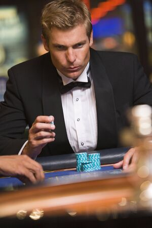 gambling parlour: Man in casino playing roulette (selective focus) Stock Photo