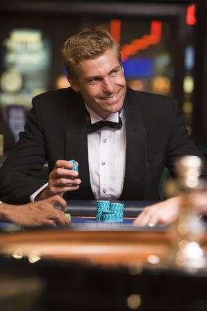 gambling parlour: Man in casino playing roulette and smiling (selective focus)