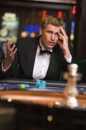 gamers: Man in casino playing roulette and losing (selective focus)