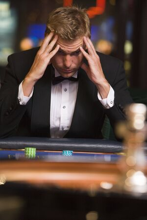 gambling parlors: Man in casino playing roulette and losing (selective focus)