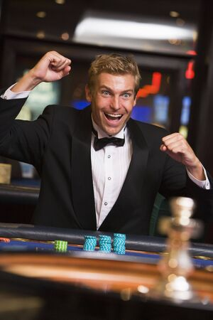 gambling parlour: Man in casino winning at roulette and smiling (selective focus)