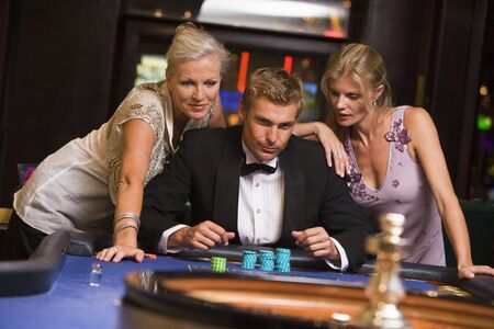 gambling parlour: Three people in casino playing roulette smiling (selective focus) Stock Photo