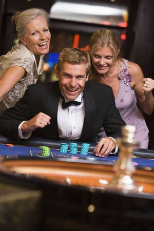 Three people in casino playing roulette smiling (selective focus) photo