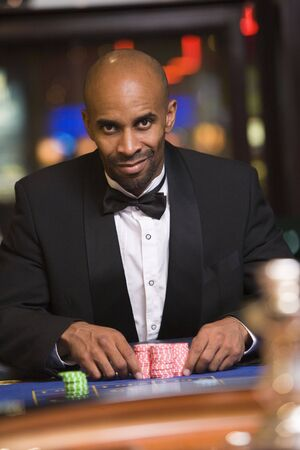 gambling parlour: Man in casino playing roulette smiling (selective focus)