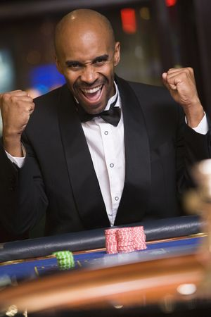 gambling parlour: Man in casino winning roulette and smiling (selective focus)