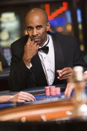 gambling parlors: Man in casino playing roulette (selective focus) Stock Photo