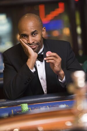 gambling parlors: Man in casino playing roulette and holding chip (selective focus)