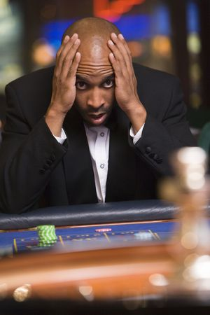 Man in casino playing roulette and losing (selective focus) photo
