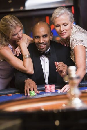 parlour games: Three people in casino playing roulette smiling (selective focus) Stock Photo