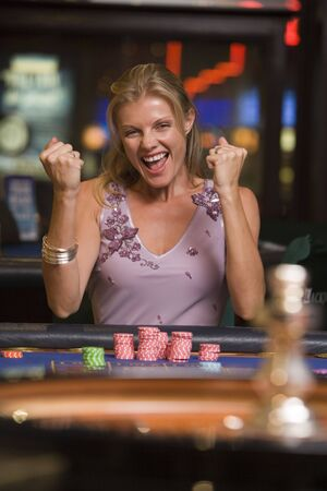 parlour games: Woman in casino winning roulette smiling (selective focus)