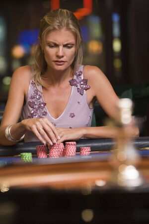 gambling parlors: Woman in casino playing roulette and thinking (selective focus)