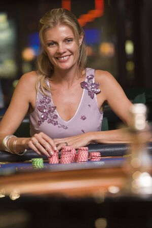 gambling parlour: Woman in casino playing roulette smiling (selective focus)